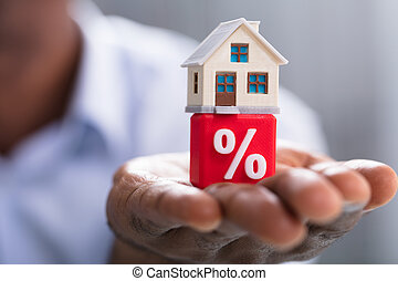 Miniature House On Percentage Block Over The Hand