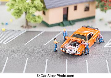 Miniature mechanics working on car - Miniature mechanics...