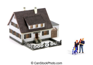 Miniature model home with a family in front