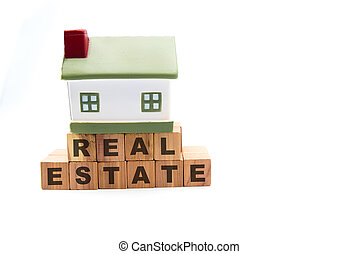 Miniature model house on fundation of real estate wooden cubes, isolated on white