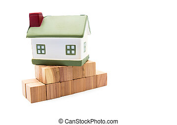Miniature model house on fundation of wooden cubes, isolated on white