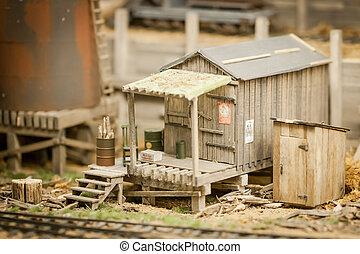 miniature model of a rundown shack beside a railroad - shallow d.o.f.