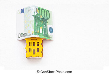 miniature of house under the Euro money folded in the shape of a house isolated on white background