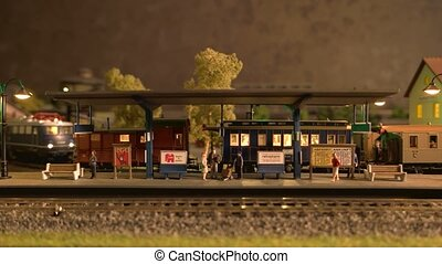 Miniature of railway station with moving train. Toy ...
