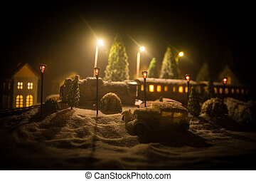 Miniature of winter scene with Christmas houses, train station, trees, covered in snow. Nights scene. New year or Christmas concept.