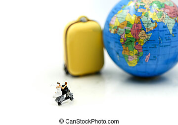 Miniature people : a newlywed couple riding the motorcycle on wolrd background for their honeymoon.