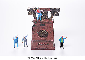 miniature people and vintage telephone on white background