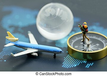 Miniature people : backpackers traveler standing with compass on the map, travel concept
