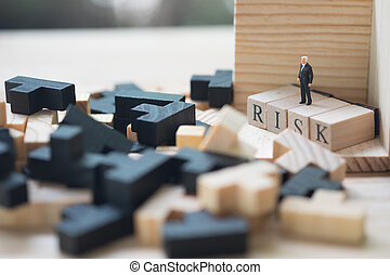 Miniature people : businessman standing on a wood cube word with risk.