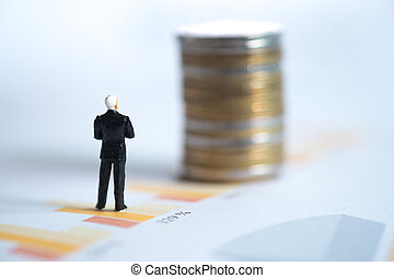 Miniature people: Businessman standing on graph with looking to coins
