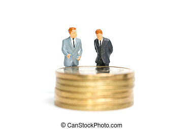 Miniature people: Businessman standing on stack of coin