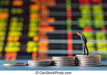 Miniature people , Businessman standing on stack of Coins with graph display background