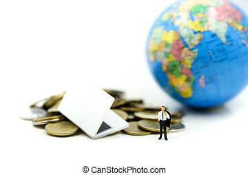 Miniature people: Businessman with Laptop and stack of coins of Mini world background saving, investment, money, financial, business concept.