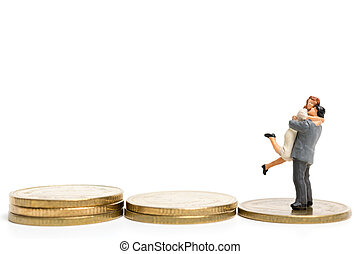 Miniature people: Couple hugging standing on stack of coin