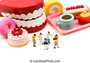 Miniature people : Doctor dentist speaks about student and children with desserts, Fun eating and healthcare concept.