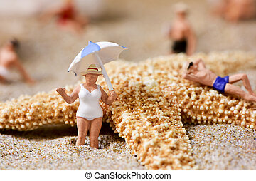 miniature people in swimsuit on the beach