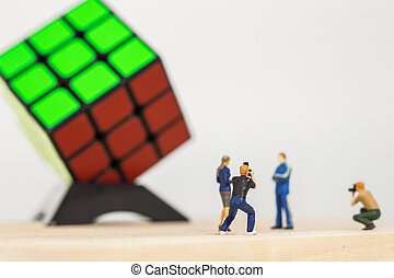Miniature people : Male photographer taking a picture of Rubik's winner 3x3 Rubik's cube on white background
