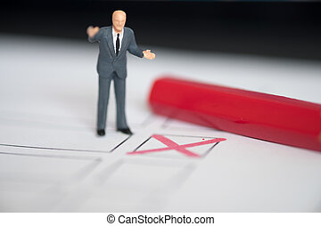 Miniature people of a politician standing on election ballot