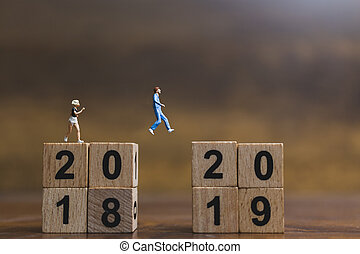 Miniature people  Running on wooden block number 2019