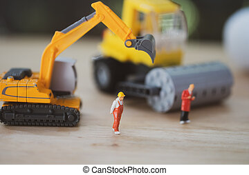 Miniature people : Worker team with yellow construction machinery models