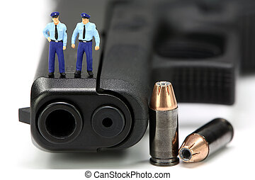 Miniature policemen standing on a gun. There are two...