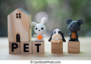 """Miniature rabbit, dog and rat on wood block word of """"PET"""" with miniature wood home. Concept of love pet"""