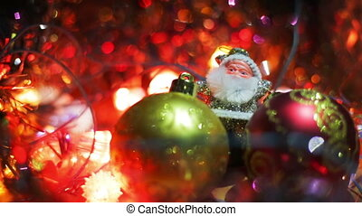 Miniature Santa Claus figure between two toy Hanging Baubles for a Christmas tree. Silver Santa on a wooden surface surrounded by flashing lights.