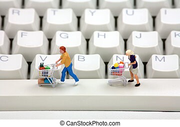 Online shopping concept. - Miniature shoppers with shopping...