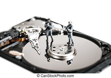 Miniature soldiers protecting computer hard drive. Technology concept.