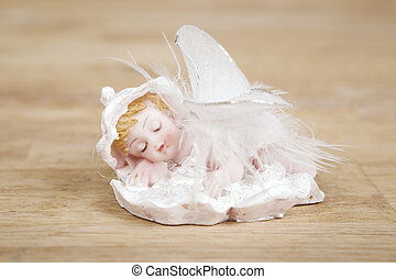 Miniature statue of white angel with wings on wooden surface.