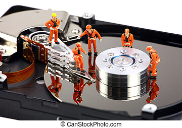 Miniature technicians work on hard drive