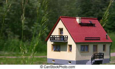 miniature toy house outdoor, green forest in background