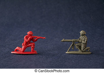 Miniature toy soldiers fighting. Plastic toy military men models attack at war.