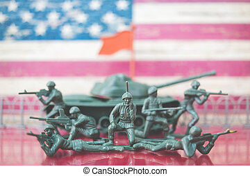 Miniature toy soldiers in battle scene with american flag background