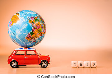 Miniature Toy vintage car carrying a world map balloon and Trip word. Travel and transport concept.