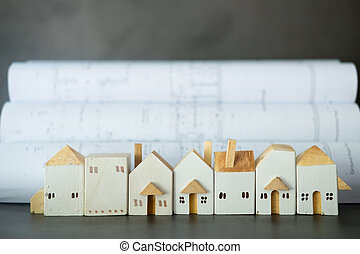 Miniature wooden home put in front of construction plans