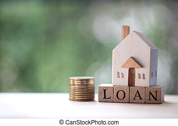 Miniature wooden home put on wooden block word with loan.
