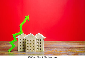 Miniature wooden houses and green arrow up. The concept of increasing the cost of housing. High demand for real estate. The growth of rent and mortgage rates. Sale of apartments. Population grows