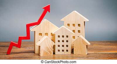 Miniature wooden houses and red arrow up. The concept of increasing the cost of housing. High demand for real estate. The growth of rent and mortgage rates. Sale of apartments. Population grows