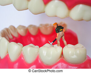Miniature worker on plastic teeth of removable denture. Dental health concept.