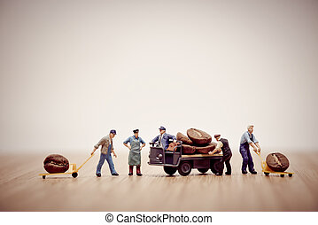Miniature workers loading coffee beans on truck