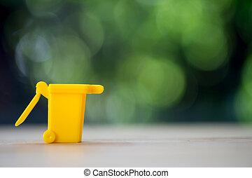 Miniature yellow garbage bin on wood table