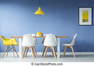 Minimal modern dining meeting room in interior with a table and a melon in a dish standing on it and contrasting white and yellow chairs around it, a yellow lamp hanging above against blue wall with a mockup poster