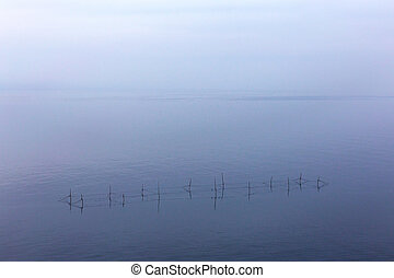 Minimalism. Seascape networks fishermen with the horizon line disappears in the low fog. Image shows a nice grain pattern at 100 percent