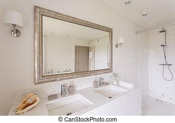 Minimalist bathroom with large mirror