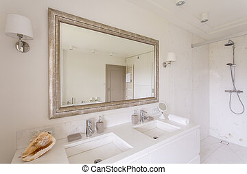 Minimalist bathroom with large mirror in a decorative frame...