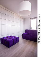 Violet hassock and couch in minimalist modern flat