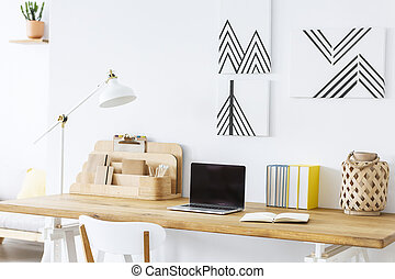 Minimalist paintings on a white wall above a wooden desk with a laptop and notebooks in a scandinavian home office interior. Real photo.