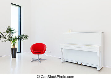 White spacious minimalist room with a piano, a red chair and a plant