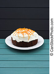 Minimalist style pastry. Homemade traditional fruit cake with cream icing and orange peel on blue background copyspace